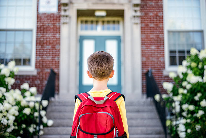 Boy wearing red backpack stands looking at the front entrance of a school by Cara Dolan for Stocksy United