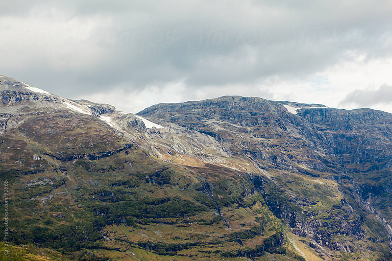 Snow on the peaks of the fjords of Norway in the summer by Cindy Prins for Stocksy United