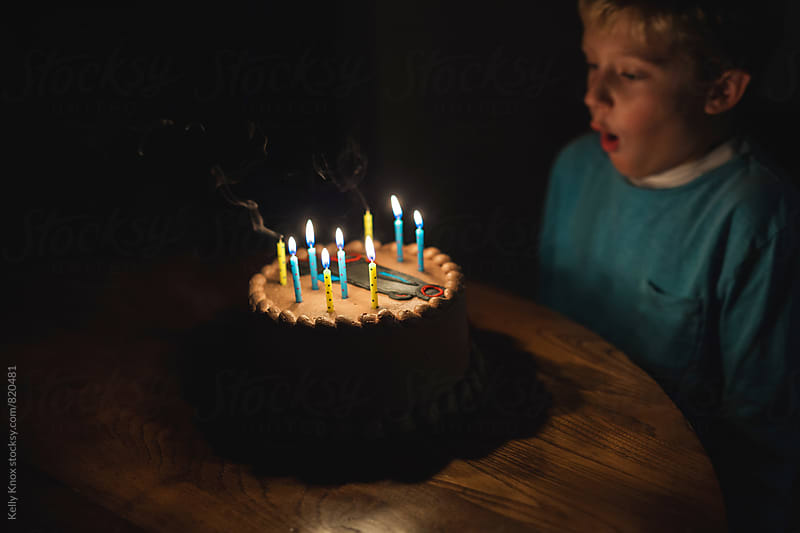 boy blowing out the candles on a birthday cake  by Kelly Knox for Stocksy United