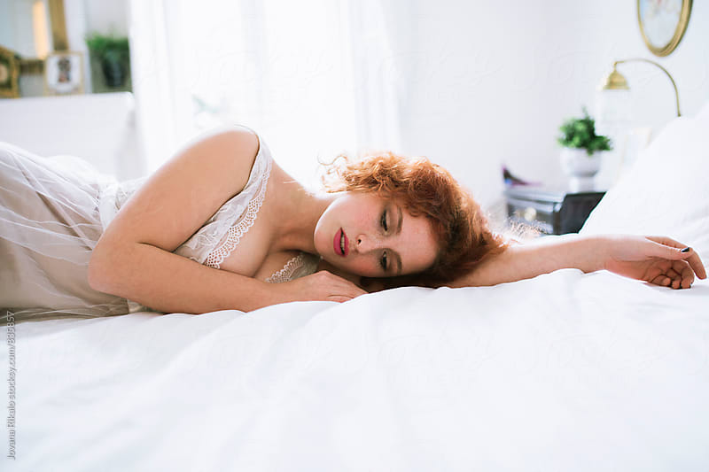 Beautiful ginger haired woman lying on a bed by Jovana Rikalo for Stocksy United