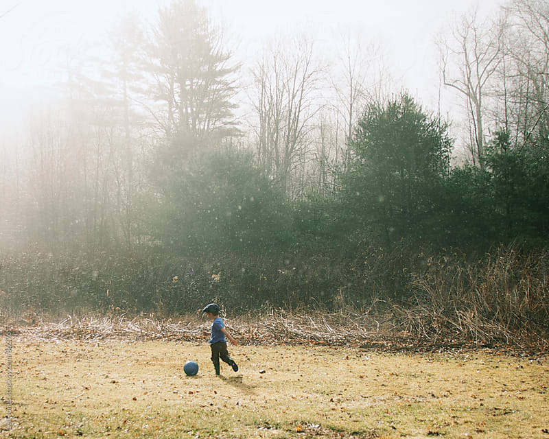 little boy playing soccer by Léa Jones for Stocksy United