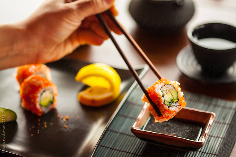 Eating Sushi in a Restaurant by Mosuno for Stocksy United
