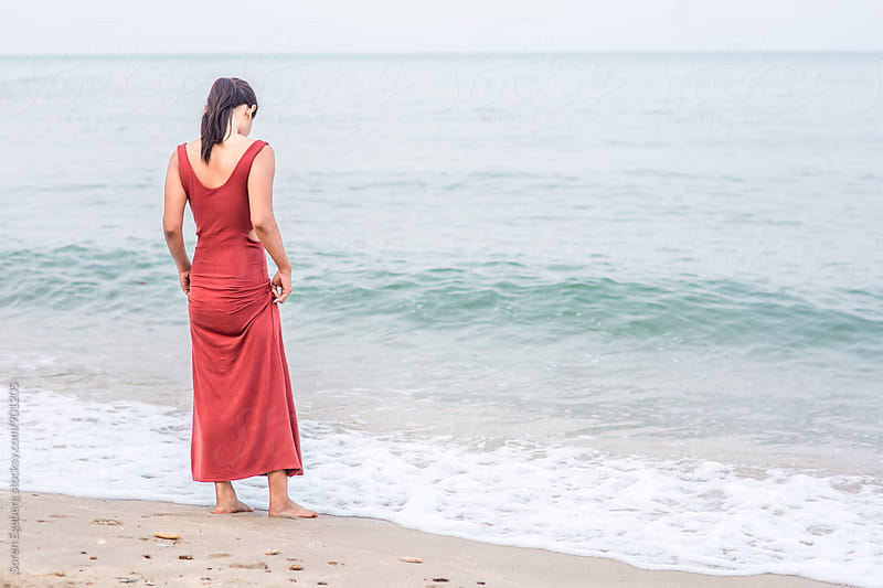 Beautiful girl standing by water edge on the beach wearing red dress by Soren Egeberg for Stocksy United