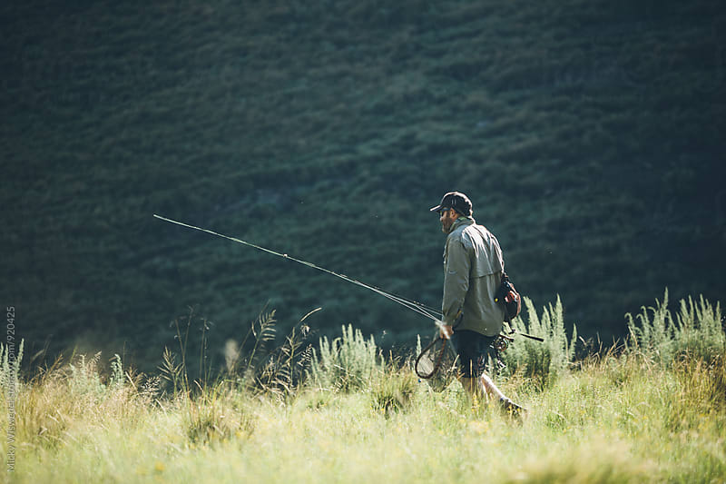 fly fisherman walking through the wilderness by Micky Wiswedel for Stocksy United