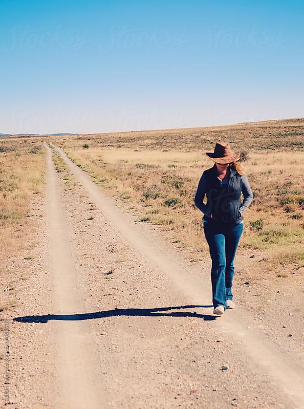 woman walking on dirt road in a flat, dry, rural scene by Gillian Vann for Stocksy United