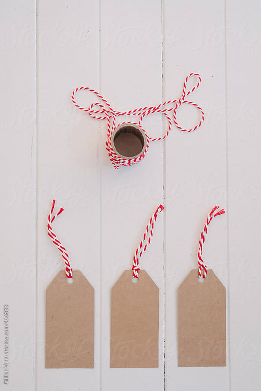 christmas tags in plain cardboard with red string by Gillian Vann for Stocksy United