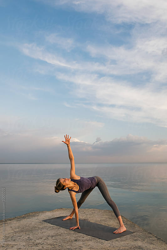 Girl doing yoga at waterfront by Danil Nevsky for Stocksy United
