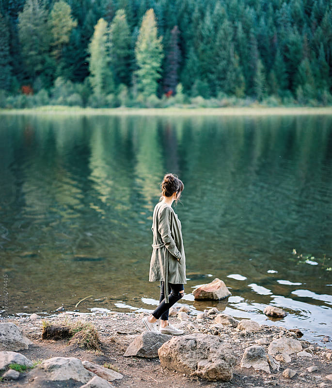 Young woman walking along lake by Daniel Kim Photography for Stocksy United