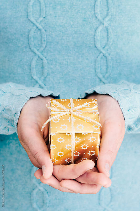 gold  christmas gift box in hands by Gillian Vann for Stocksy United