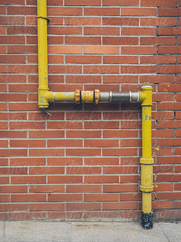 water pipe on the brick wall by unite images for Stocksy United