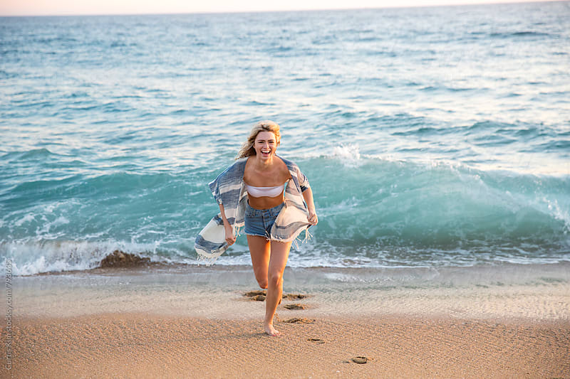 Beautiful blonde girl running on the sand at the beach by Curtis Kim for Stocksy United
