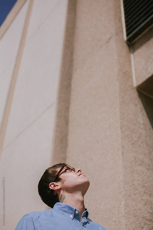 Man looking up at building by Gabrielle Lutze for Stocksy United