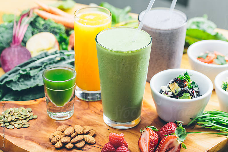 Juices smoothies and salads with raw ingredients by Lior + Lone for Stocksy United