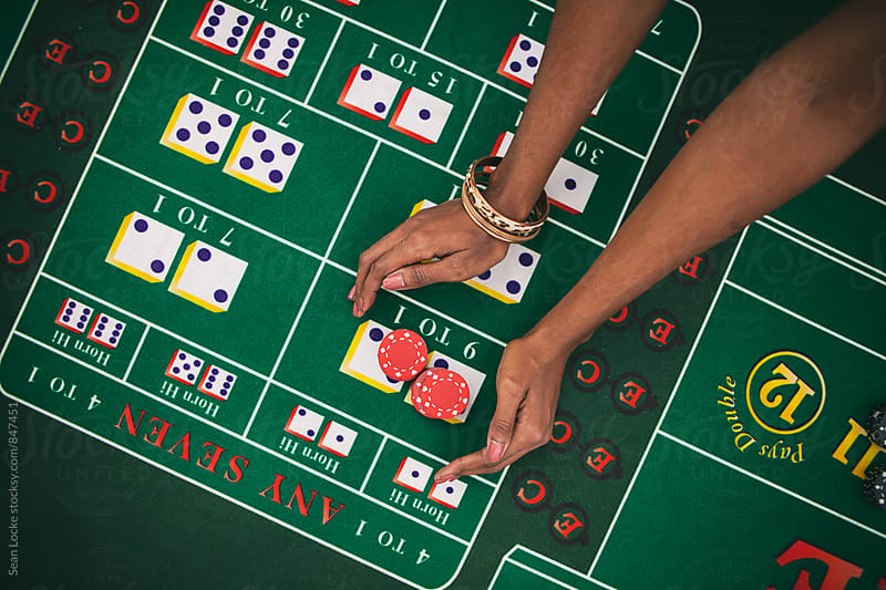 Casino: Woman Reaches Out To Grab Winnings From Craps Table by Sean Locke for Stocksy United
