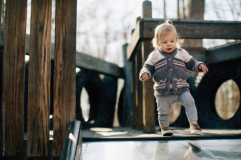 toddler playing outside on a playground by Meaghan Curry for Stocksy United