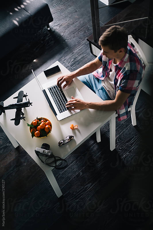 Young Designer Working on Laptop at his Home Office by Marija Savic for Stocksy United