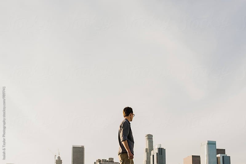 Man looking toward city by Isaiah & Taylor Photography for Stocksy United