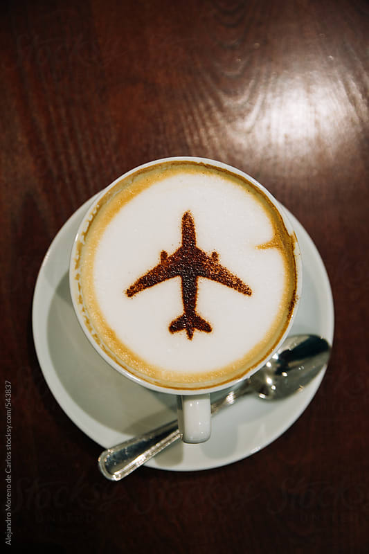 Coffee cup with an airplane made of chocolate powder on top of the foam - Travel concept by Alejandro Moreno de Carlos for Stocksy United