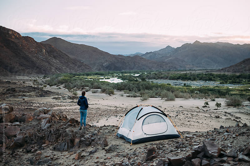 Hiker standing outside her tent in a rugged scenic desert landscape by Micky Wiswedel for Stocksy United