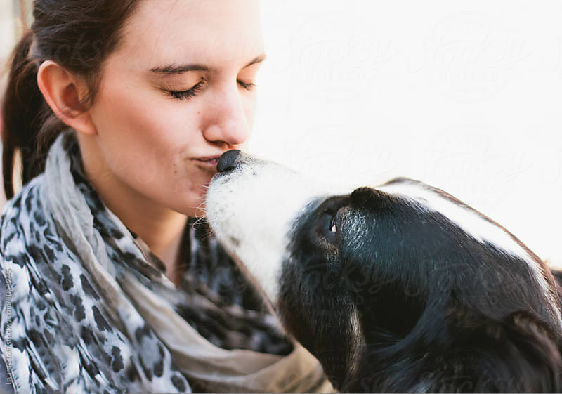 Extreme close up of shepherd dog kissing on the mouth beautiful brunette woman by Laura Stolfi for Stocksy United