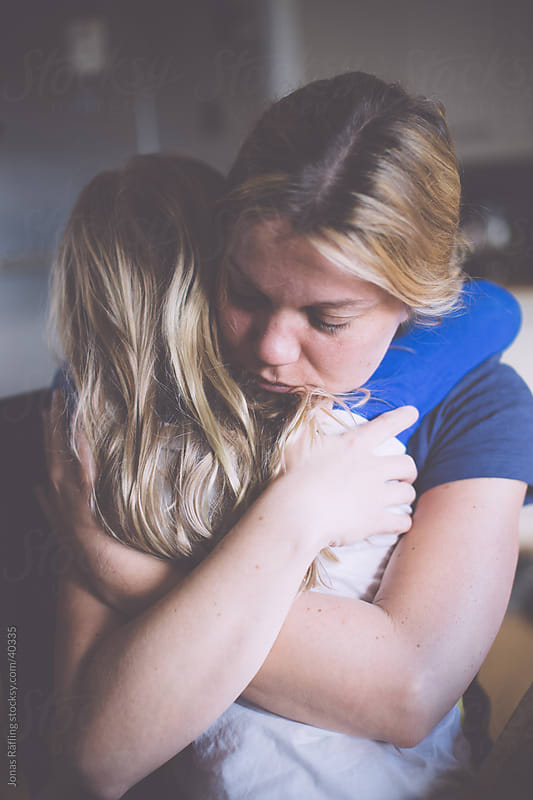 Mother hugging her daughter by Jonas Räfling for Stocksy United