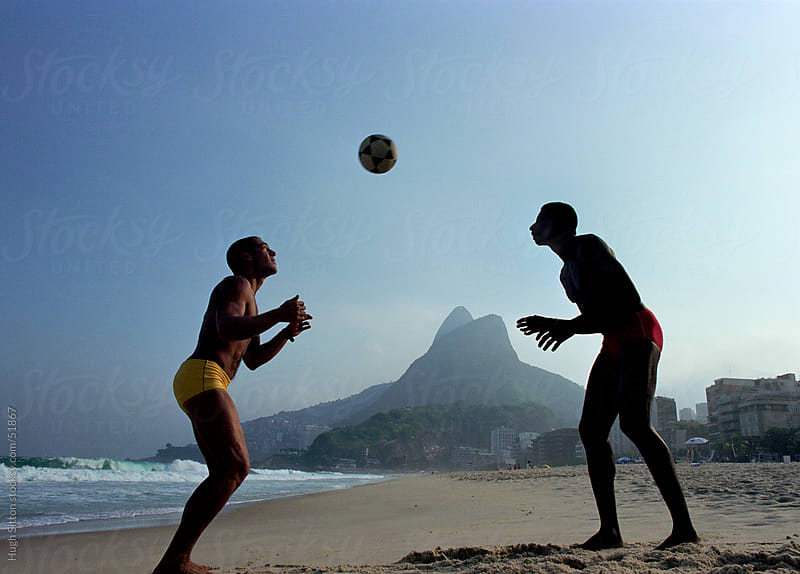 Two men playing soccer on Ipanema beach. Rio de Janeiro. Brazil by Hugh Sitton for Stocksy United