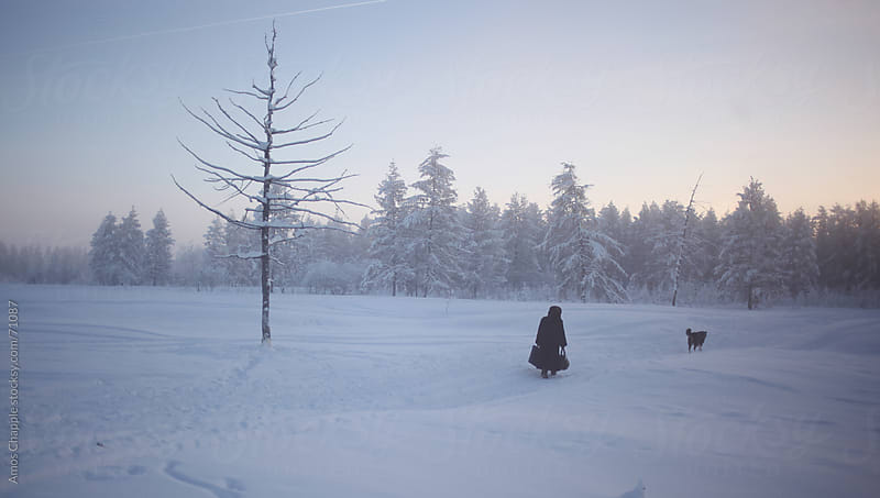 A woman walking home through the world's coldest village.  by Amos Chapple for Stocksy United
