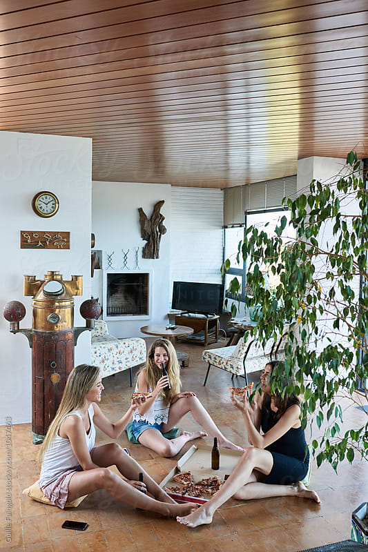 Girlfriends eating pizza with beer in modern living room by Guille Faingold for Stocksy United