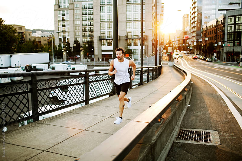 Man running on city street by Isaac Lane Koval for Stocksy United