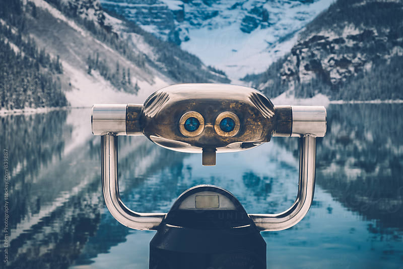 A viewfinder in front of the beautiful mountain scenery of Lake Louise in winter by Sarah Ehlen Photography for Stocksy United