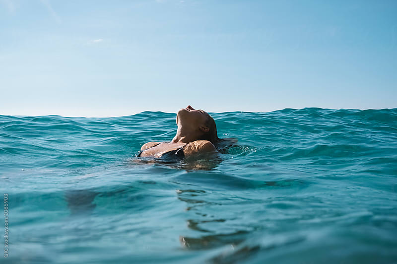 Young woman relaxing in the sea by WAVE for Stocksy United