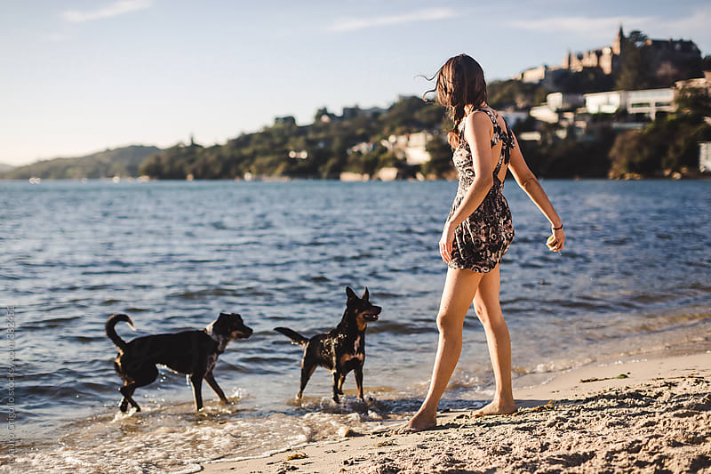 Woman playing on the beach with her dogs by Mauro Grigollo for Stocksy United