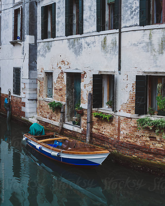 Motor boat moored near the door of Venitian house by Trent Lanz for Stocksy United