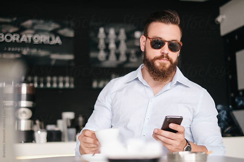 Handsome Man with Sunglasses  Sitting at the Cafe and Using Phone by Branislav Jovanović for Stocksy United