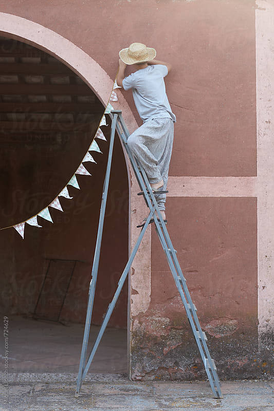 Young man on a ladder decorating a party by Miquel Llonch for Stocksy United