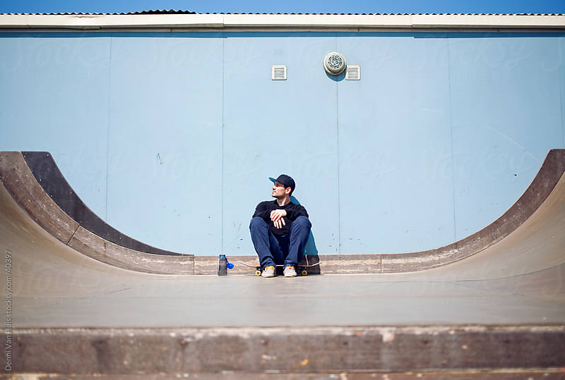 Young man sitting down to take a break from skateboarding by Denni Van Huis for Stocksy United