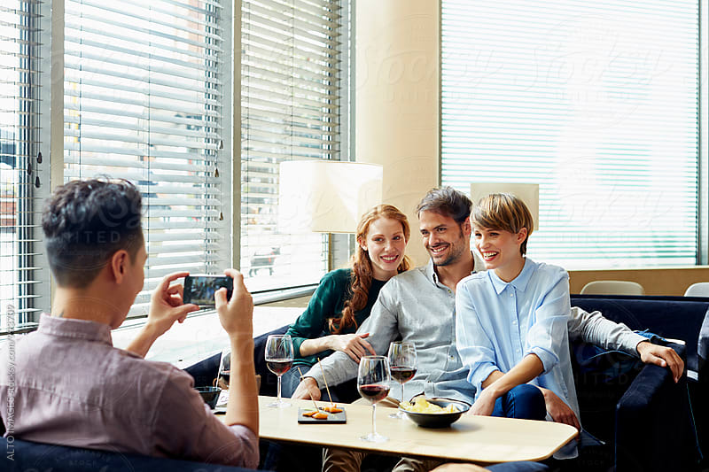 Man Photographing Friends In Restaurant by ALTO IMAGES for Stocksy United