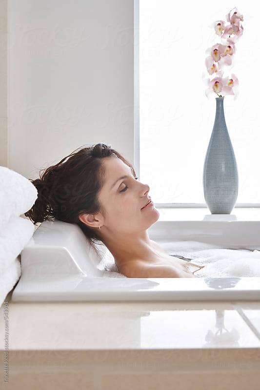 Woman taking a bath in luxury bathroom  by Trinette Reed for Stocksy United