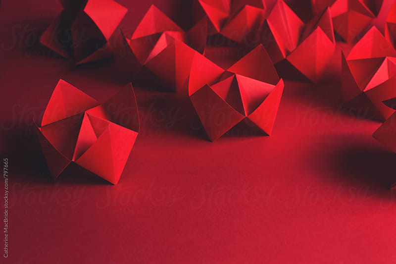 Folded red paper fortune tellers on red... by Catherine MacBride for Stocksy United