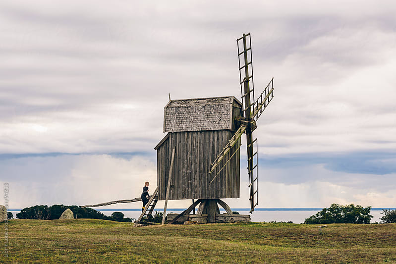 Woman climbing steps into old windmill  by Lior + Lone for Stocksy United