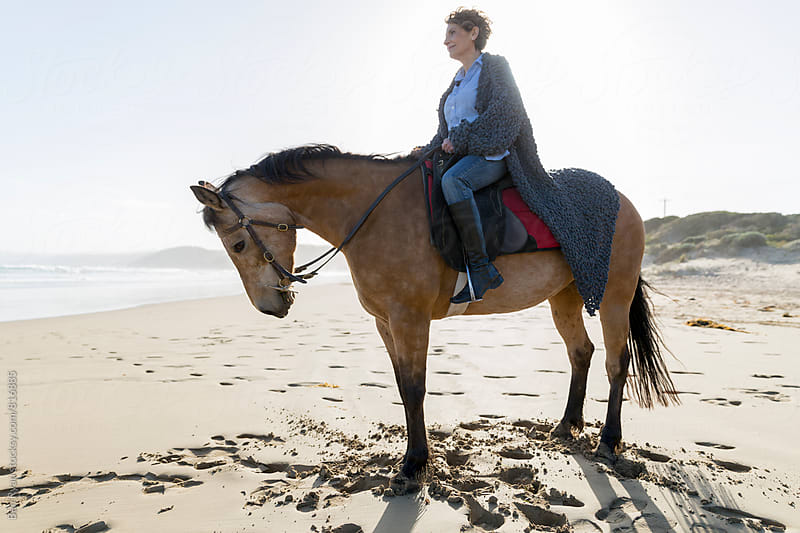Profile view of senior female riding horseback on beach with long coat draped behind her by Ben Ryan for Stocksy United