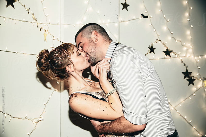 A young couple kissing at New Years  by Shaun Robinson for Stocksy United