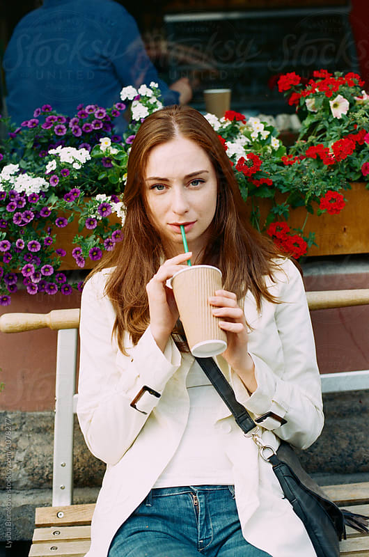Young woman drinking milkshake outdoors by Lyuba Burakova for Stocksy United