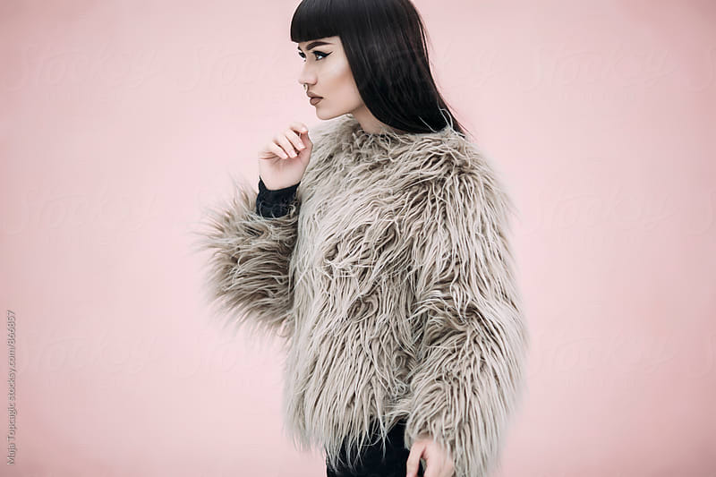 Beautiful woman in fur coat in front of pink background by Maja Topcagic for Stocksy United