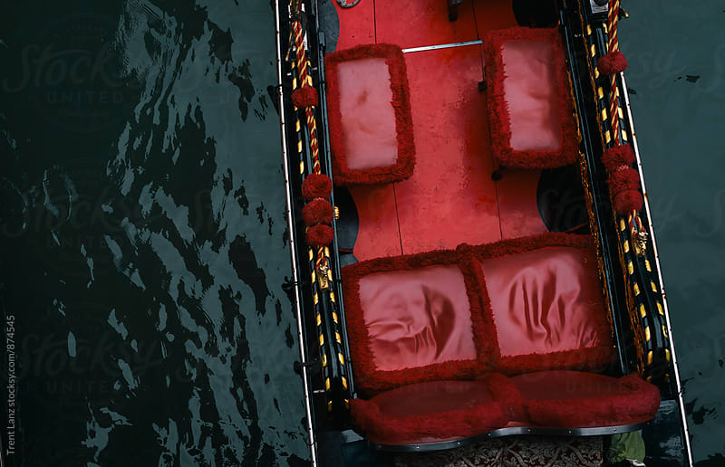 View on gondola boat with red seats floating on water by Trent Lanz for Stocksy United