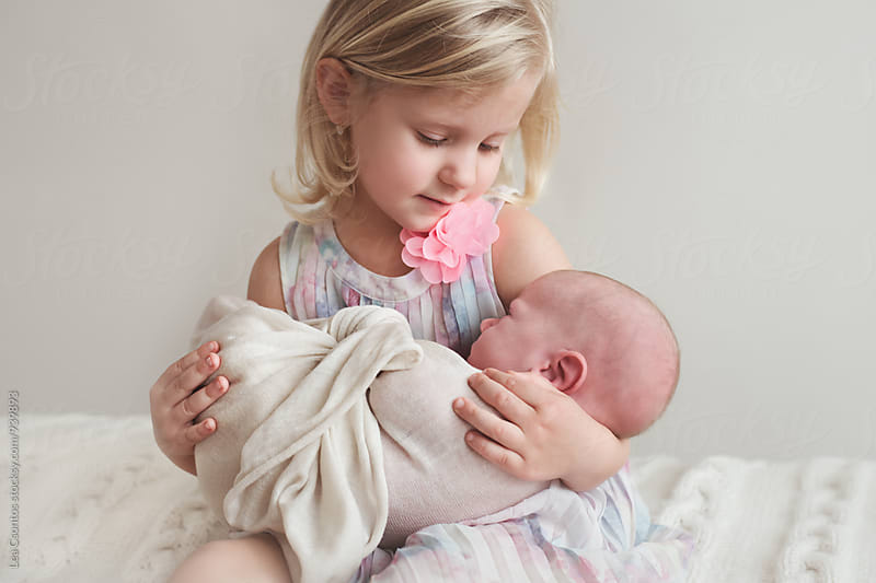 Little girl holding her baby brother in her arms by Lea Csontos for Stocksy United
