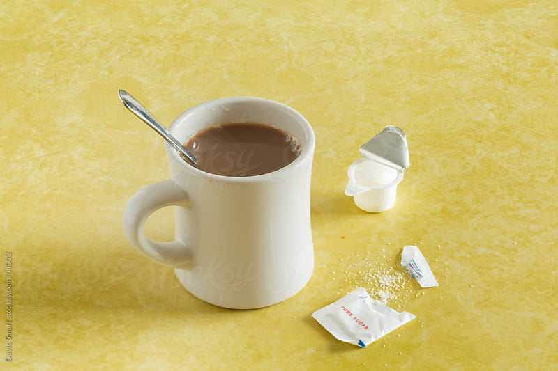 Retro coffee mug, spoon, sugar packet and creamer on diner counter by David Smart for Stocksy United