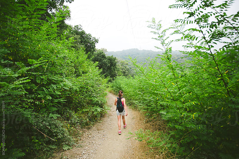 Back view of young hiker woman with backpack on a forest road. by BONNINSTUDIO for Stocksy United