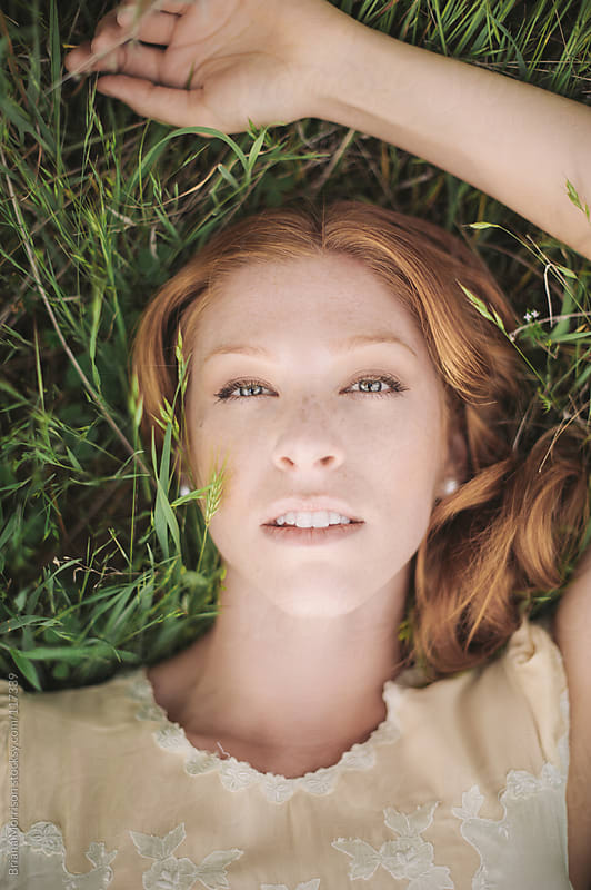 Woman with Red Hair Resting in Green Grass Field by Briana Morrison for Stocksy United