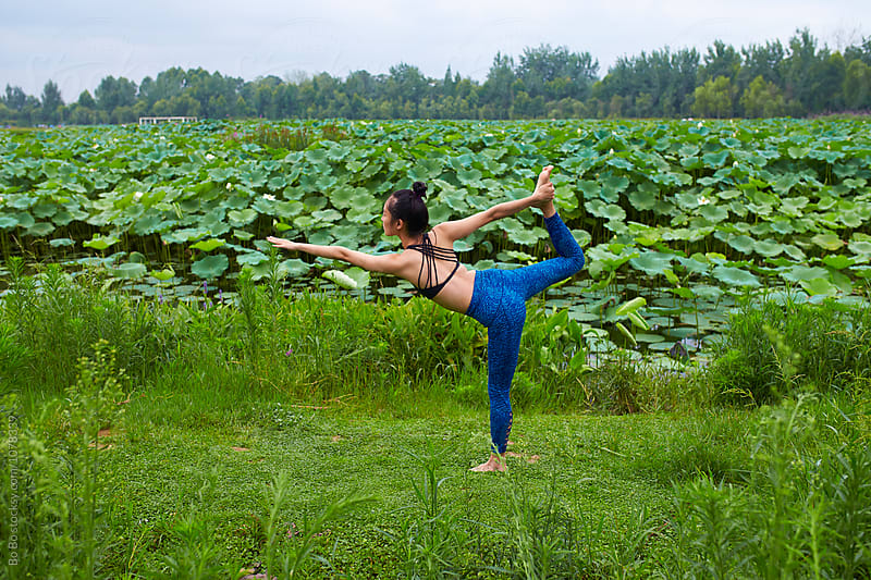 young asian or Chinese woman exercise Yoga by the side of lotus pond by cuiyan Liu for Stocksy United